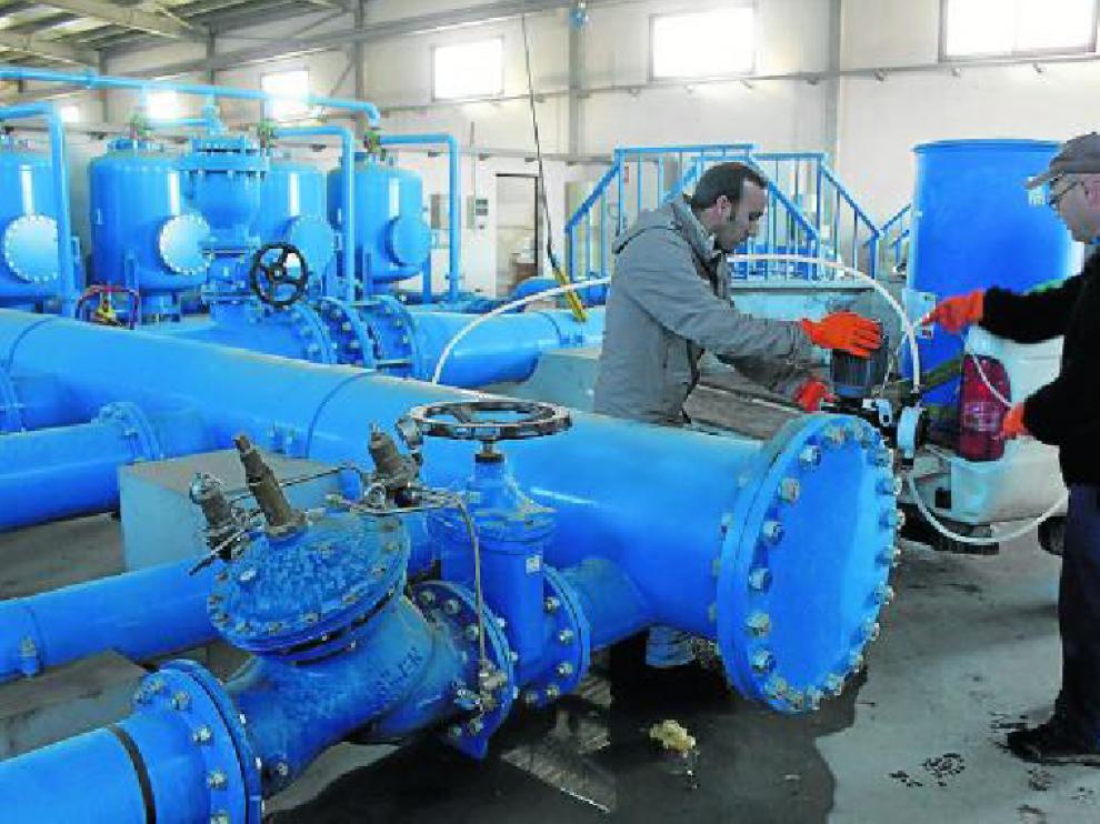 Dos técnicos de la comunidad de Almudévar durante la inyección de peróxido de hidrógeno.