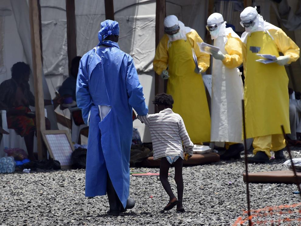 Una enfermera camina de la mano de una niña pequeña enferma de ébola, en un Centro de Médicos Sin Fronteras de Monrovia.