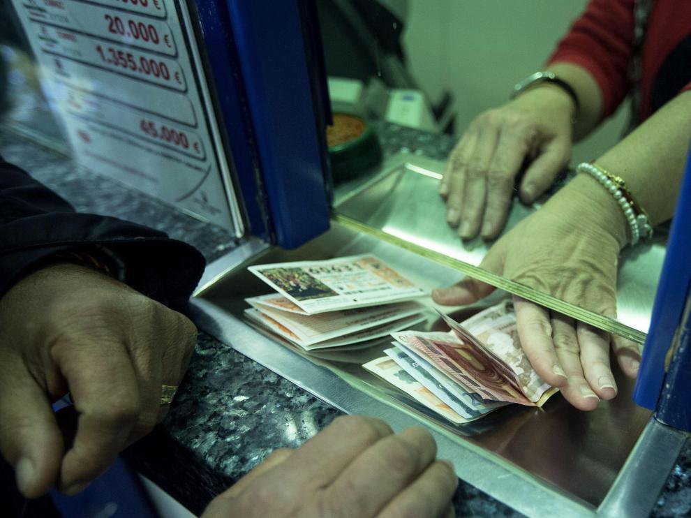 Un hombre compra varios décimos en una administración de lotería