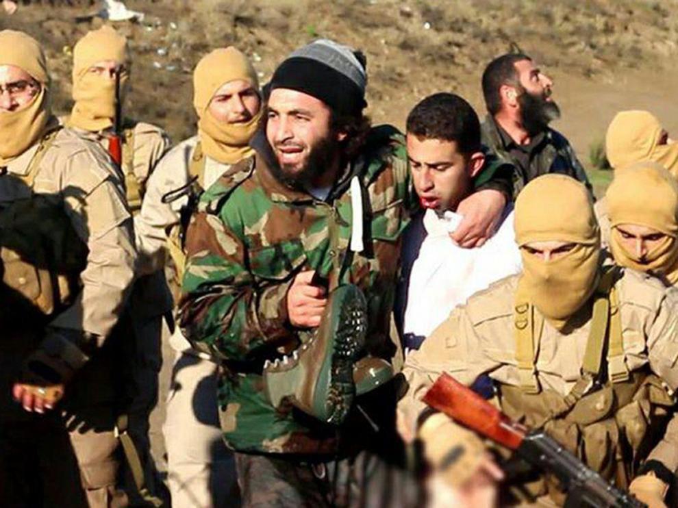Milicianos del EI con el supuesto piloto jordano capturado