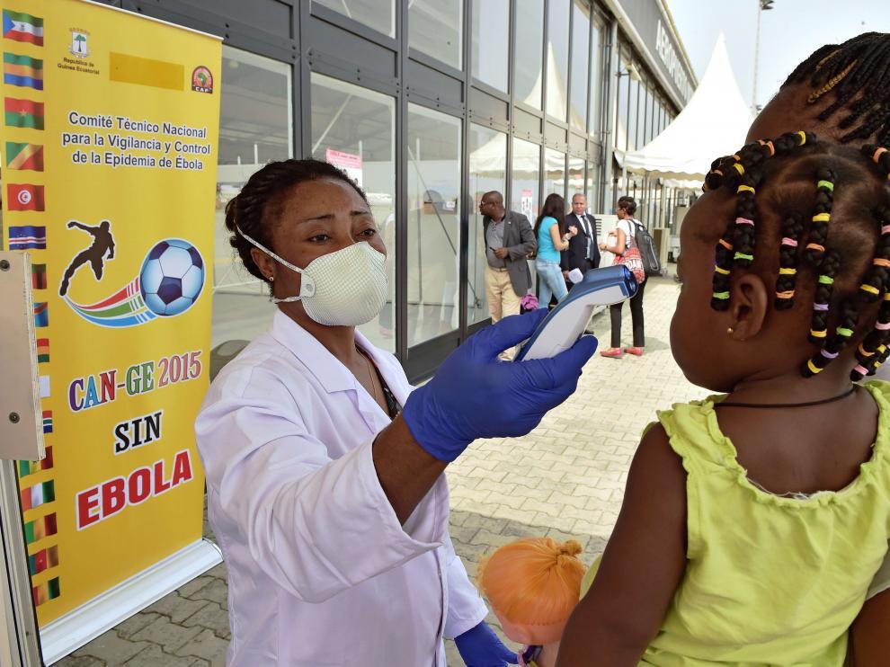 Una trabajadora sanitaria comprueba la temperatura de una niña pequeña en el aeropuerto de Bata (Guinea).