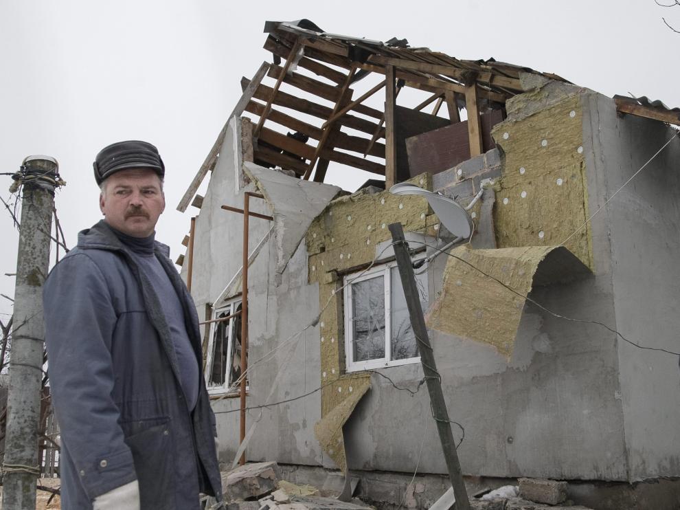 Un vecino de Donetsk, junto a su casa destruida