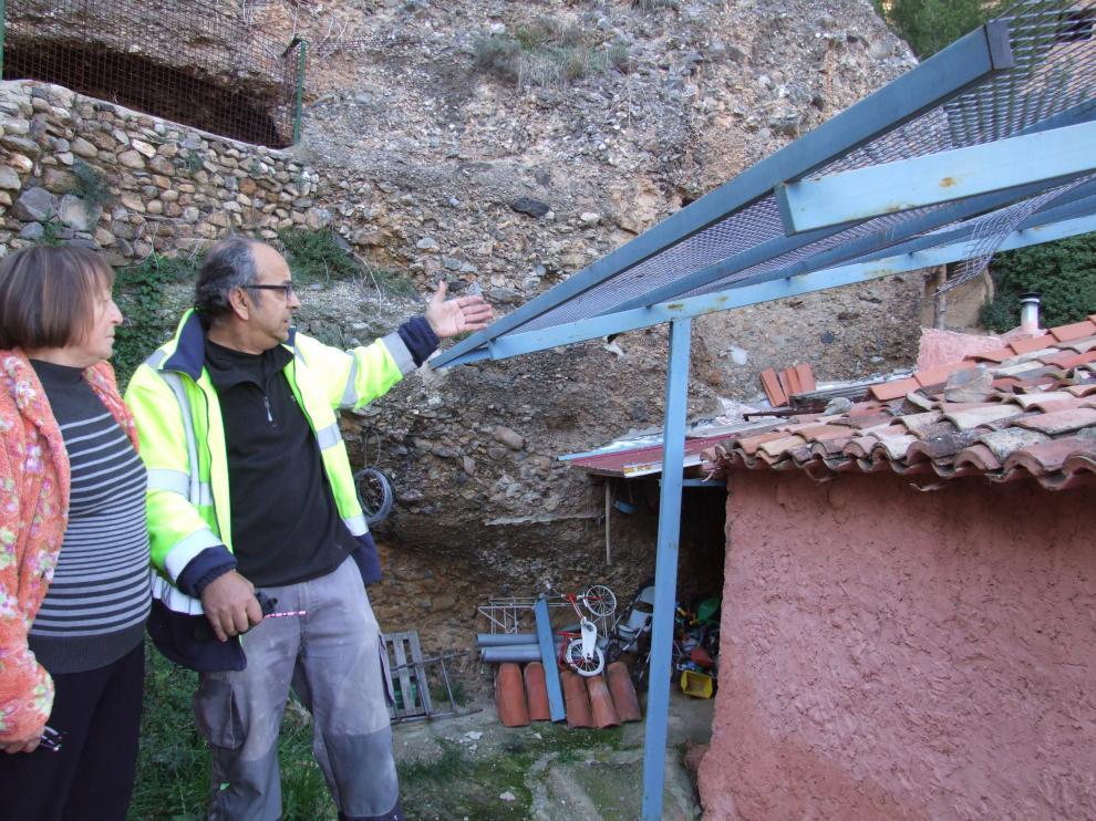 El alguacil y una vecina de Los Fayos frente al tejado donde cayó la última piedra.