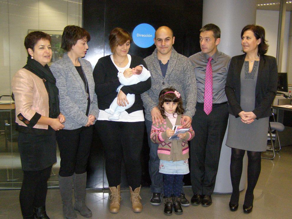 La familia del primer bebé posa con responsables de ACT y La Caixa.