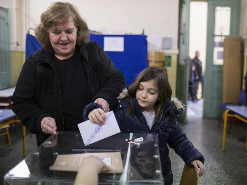 Una griega con su hija deposita su voto a primera hora de la mañana en un colegio electoral de Atenas, este domingo, 25 de enero