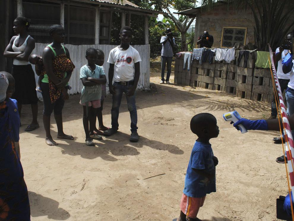 Un médico toma la temperatura a un niño en un barrio de Monrovia, en Liberia, el pasado miércoles