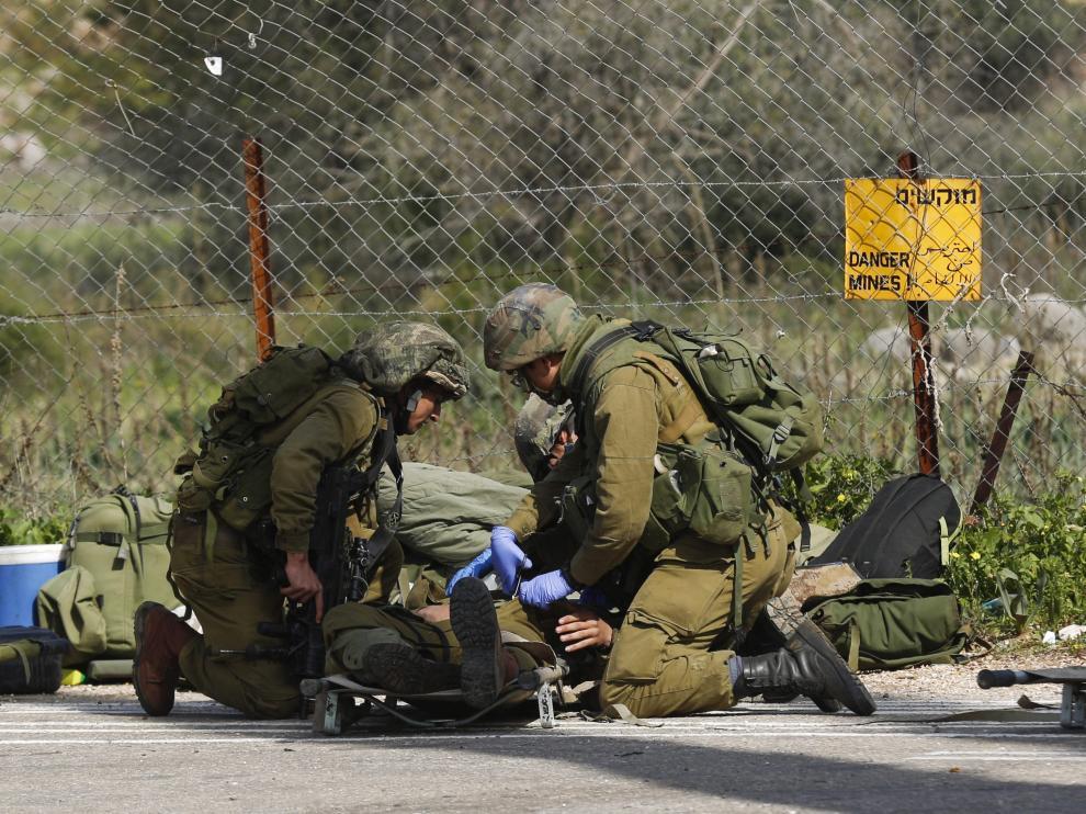 Un soldado isrelí herido recibe atención médica de varios compañeros después de que impactara un misil antitanques en su vehículo