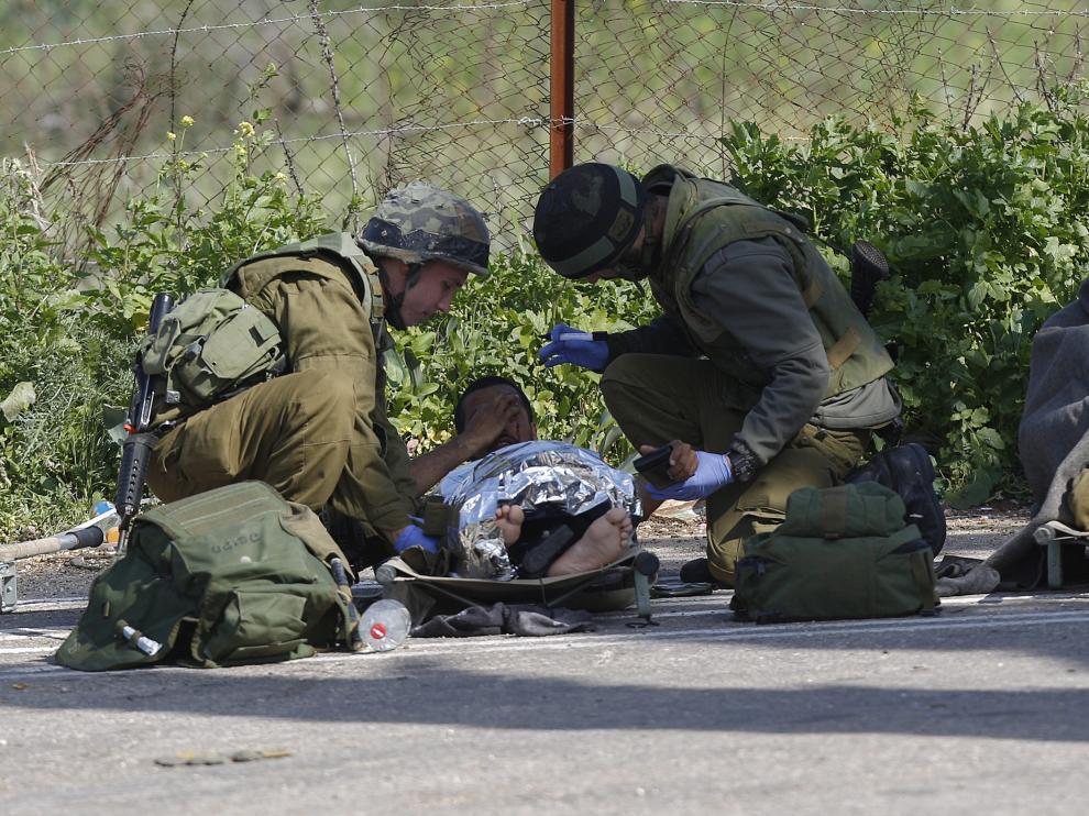 Un soldado isrelí herido recibe atención médica de varios compañeros después de que impactara un misil antitanques en su vehículo cerca de la zona de Har Dov