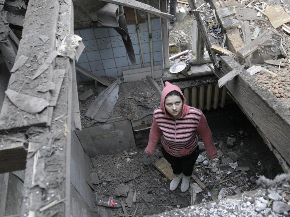 Una mujer observa los restos de su casa destruida en el centro de Donetsk, al este de Ucrania