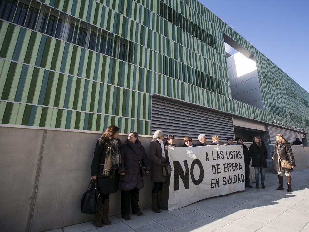 Un grupo de miembros de la Asociación de Vecinos de la Almozara ha recibido a Rudi y Oliván con una pancarta en la que se leía 'No a las listas de espera'.