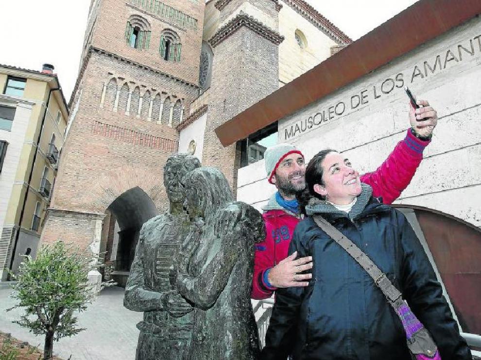 Nuria y Fernando, una pareja malagueña, aprovechó su visita turística a Teruel para hacerse una foto junto  a la recién inaugurada escultura de los amantes que se encuentra  lindando al mausoleo.