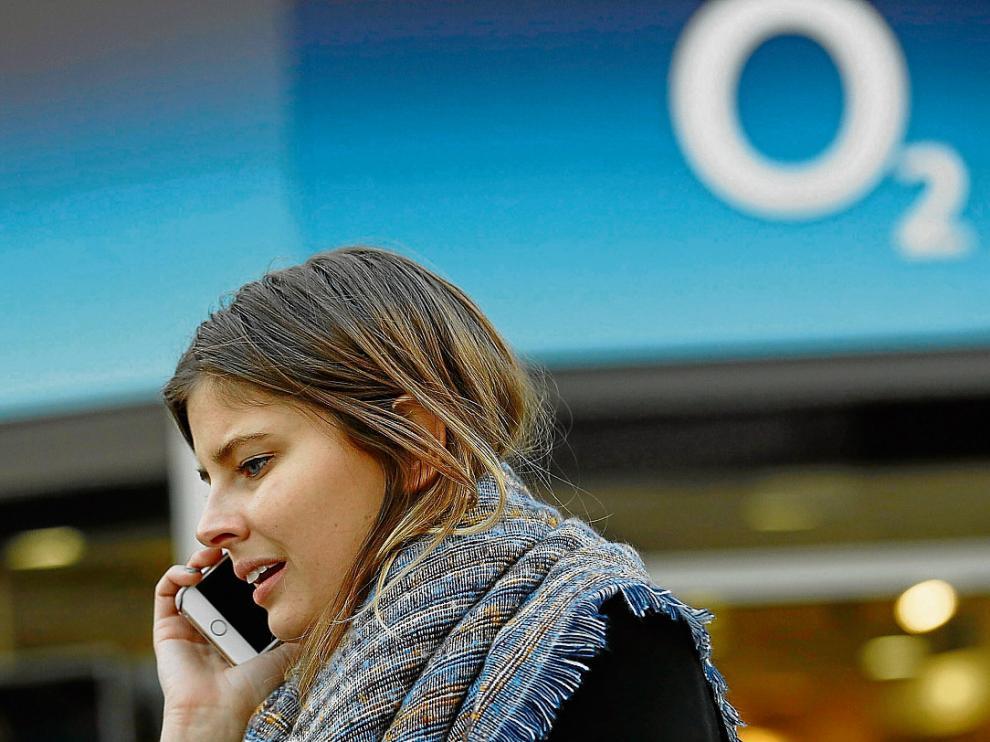 Una mujer habla por el móvil junto a la sede de una tienda de O2 en Londres.