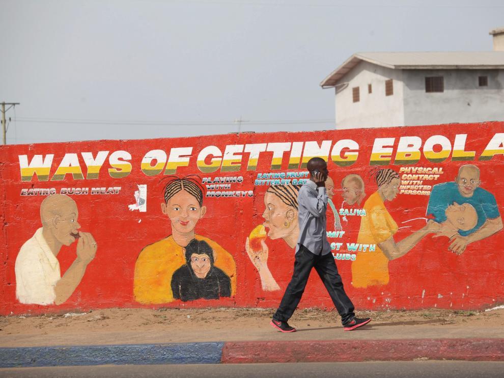 Un ciudadano de Liberia pasea por delante de un mural divulgativo pintado para concienciar sobre la epidemia de ébola.
