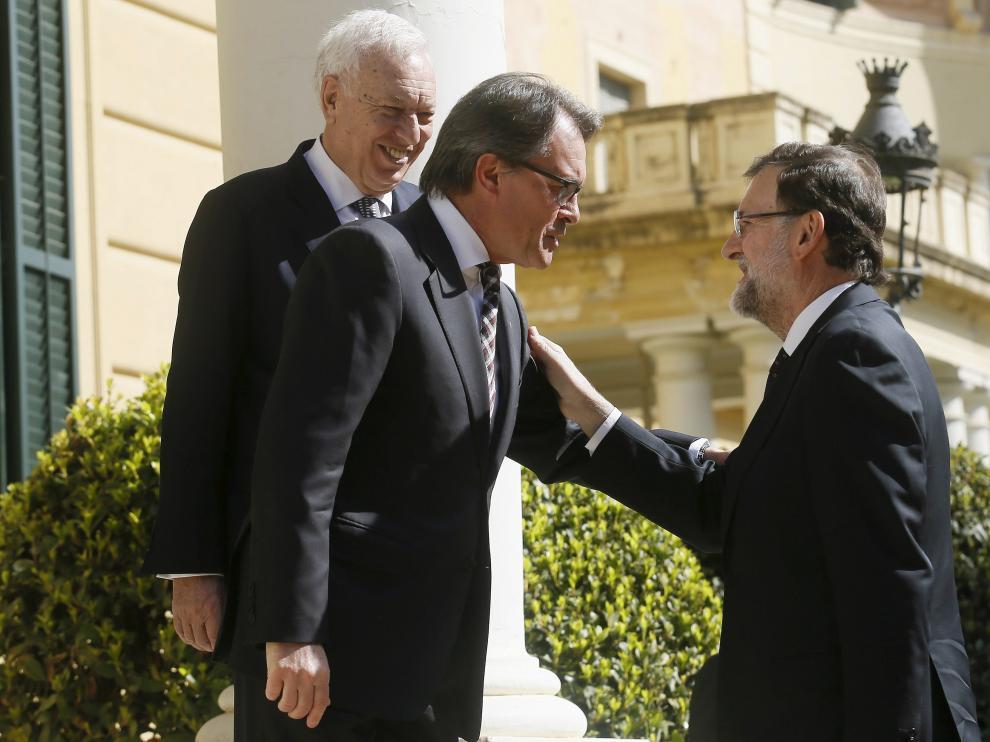 Rajoy estrecha la mano a Mas junto a Margallo.