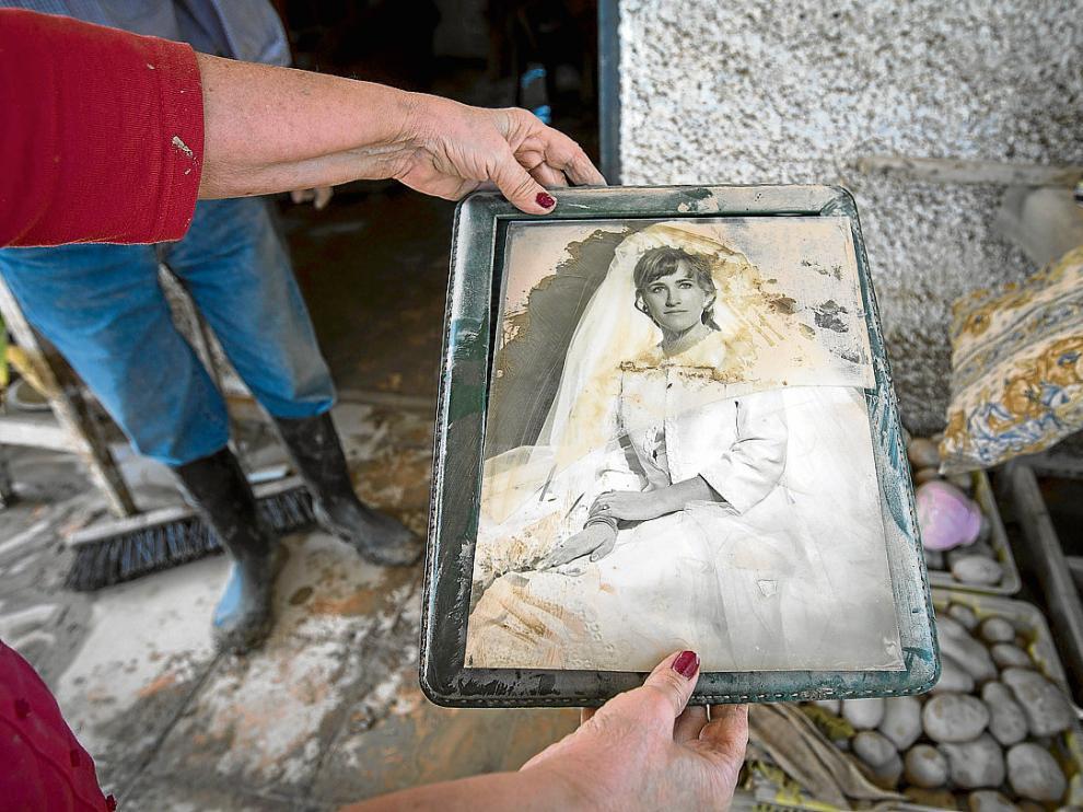 Mª Pilar Oquendo muestra el estado en el que ha quedado su foto de boda tras inundarse su casa.