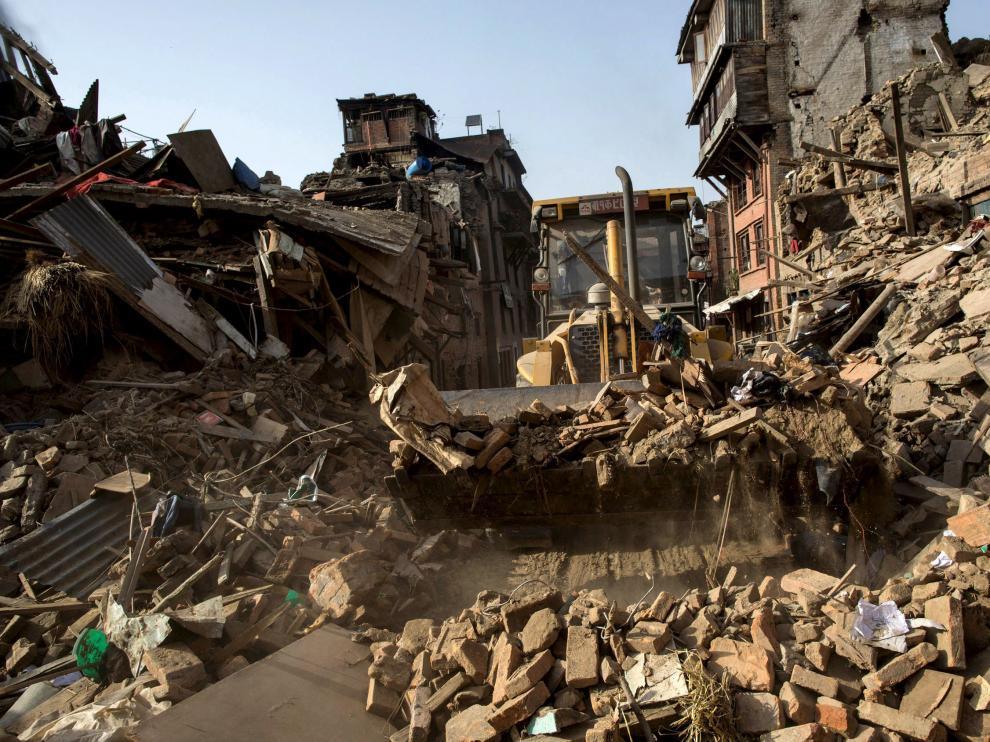 Una excavadora retira escombros en una localidad de Nepal