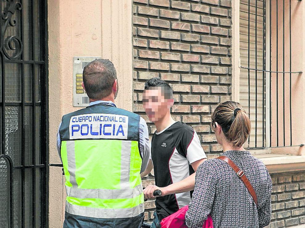 Dos policías hablan con un primo del chico tiroteado.