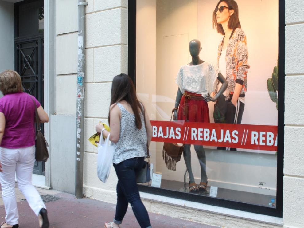 Una joven pasea junto al escaparate de un establecimiento con rebajas en Zaragoza.