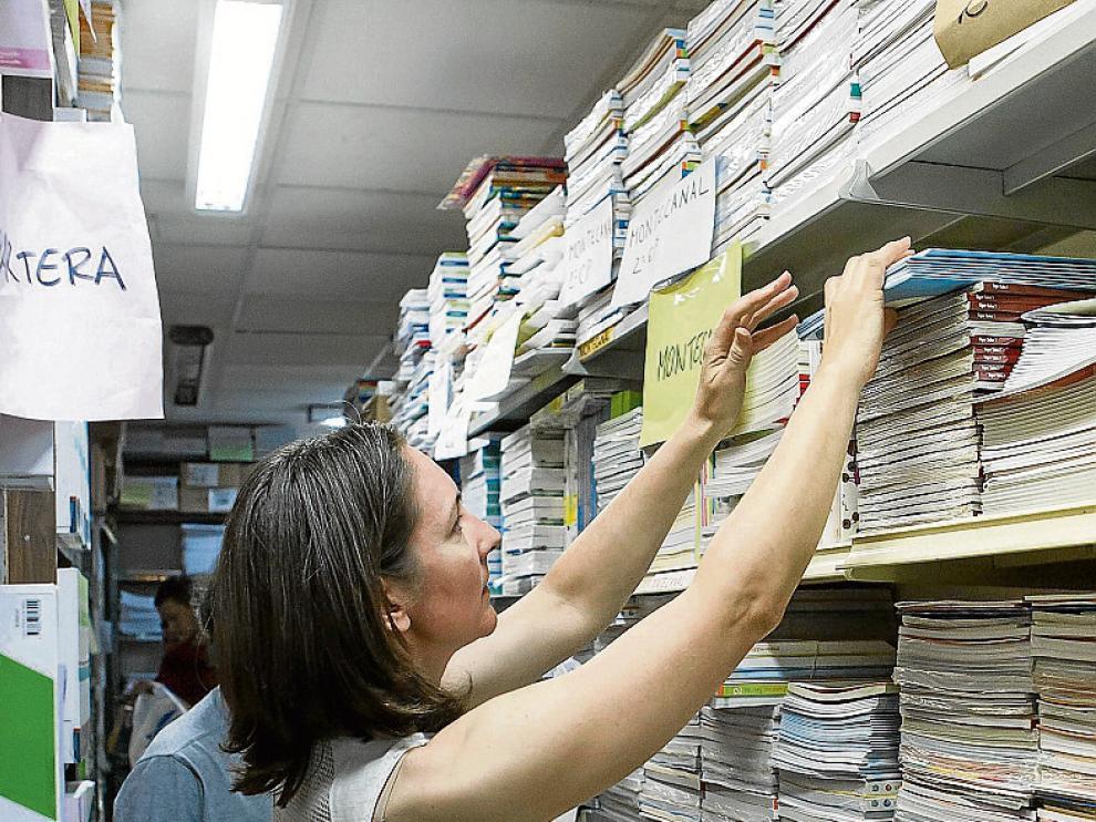 Foto de archivo de una librería ordenando libros de texto.