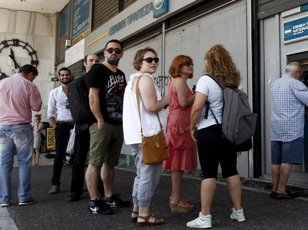 Atenienses hacen cola para retirar dinero en una sucursal del Banco Nacional de Grecia.