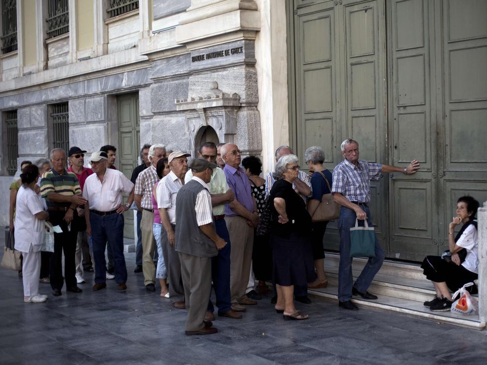 Un grupo de jubilados espera en la puerta del Banco Nacional de Gracia. (Archivo)