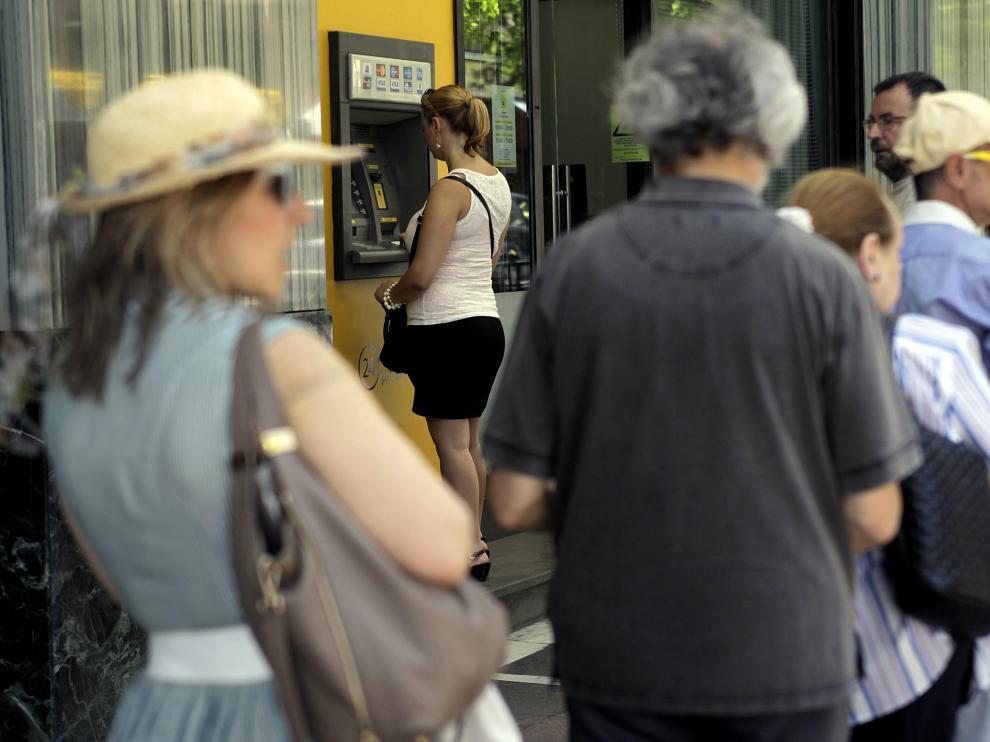 Un grupo de griegos hacen cola delante de un cajero en el centro de Atenas.
