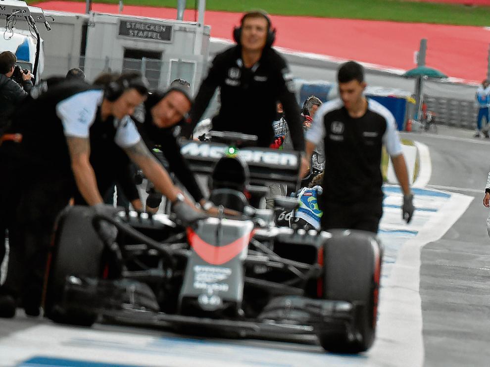 Fernando Alonso, al fondo, observa cómo retiran su monoplaza, ayer en el circuito Red Bull Ring.
