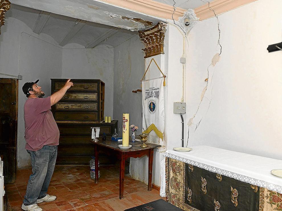 Un vecino muestra las filtraciones y las grietas que recorren la sacristía de la iglesia.