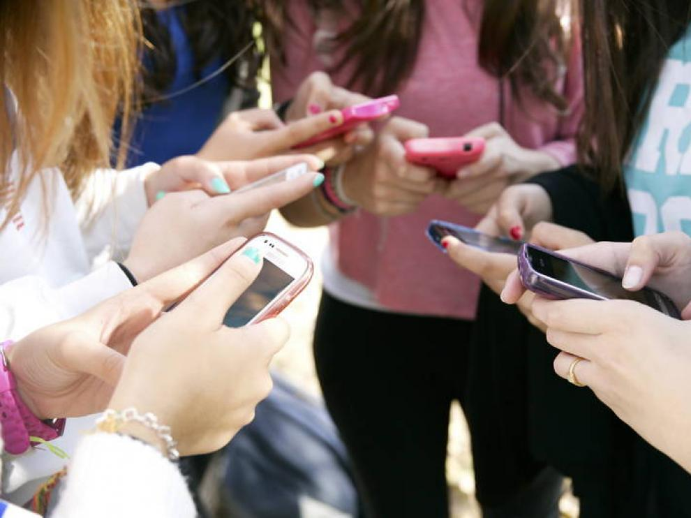 Un grupo de adolescentes usan sus teléfonos en un instituto.