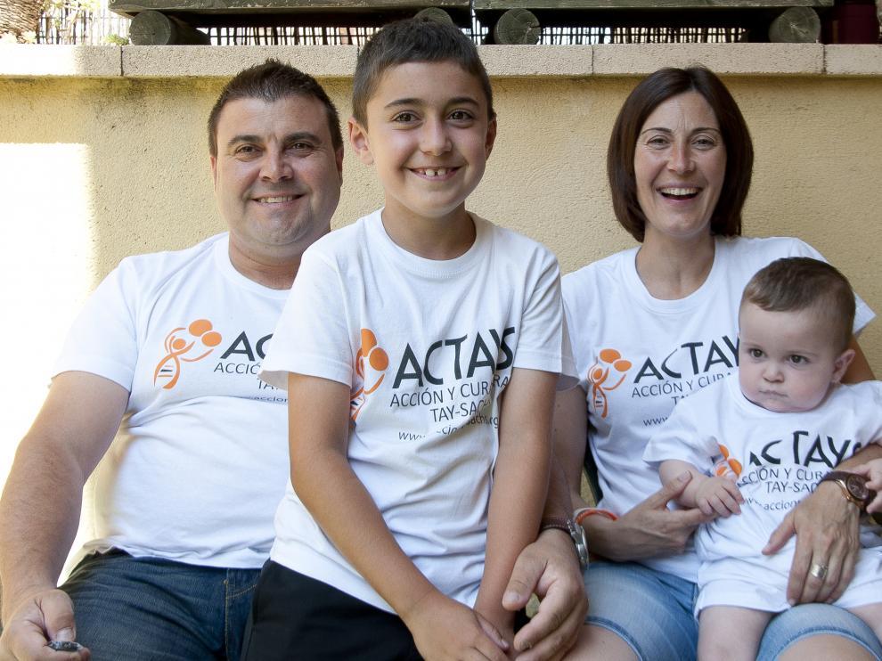 El pequeño Hugo (d), de 16 meses, junto a sus padres y su hermano vestidos con las camisetas de la asociación Actays.