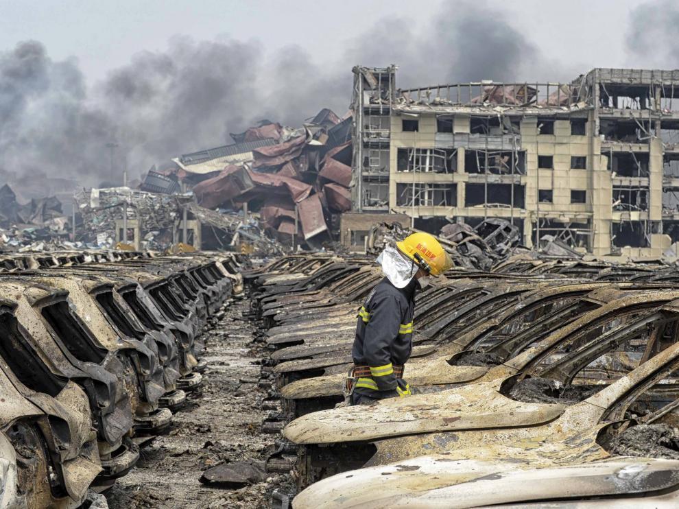 Un bombero camina sobre la zona afectada por la explosión en Tianjin
