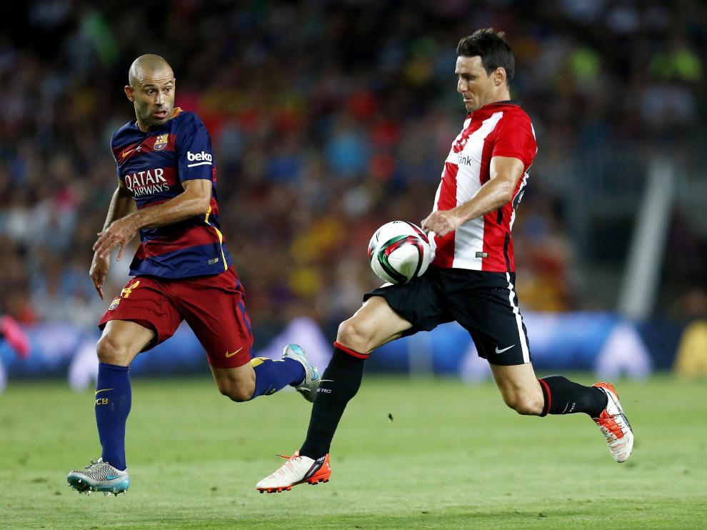 El defensa argentino del FC Barcelona Javier Mascherano (i) persigue al delantero del Athletic Club Aritz Aduriz.