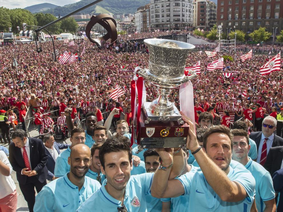 El capitán Carlos Gurpegui (c), sujeta el trofeo junto al resto de los jugadores del Athletic ante miles de personas.