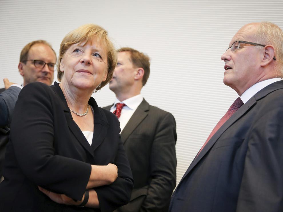 La canciller alemana, Angela Merkel, conversa con el jefe del grupo parlamentario conservador durante la reunión del lunes por la tarde.