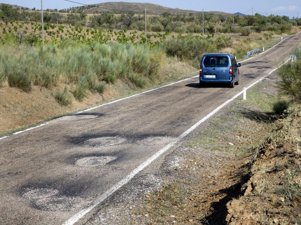 Un vehículo circula por la A-1503. La imagen muestra la calzada llena de baches recién parcheados.