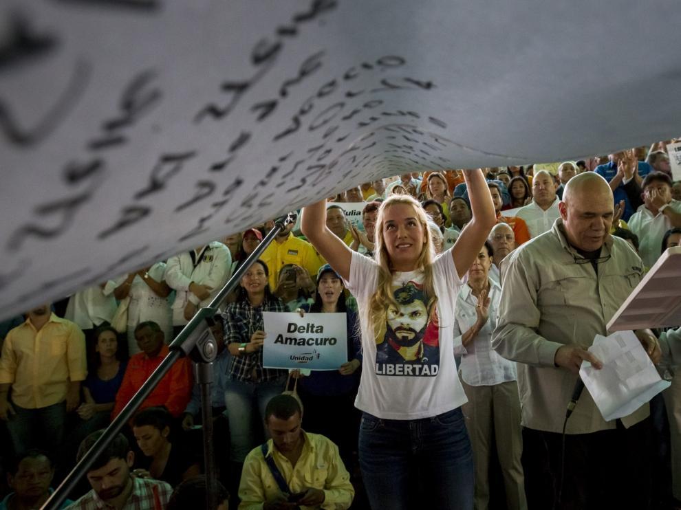 La esposa de Leopoldo López sostiene un cartel con los nombres de los presos políticos venezolanos.