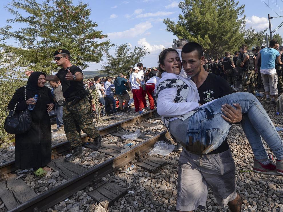 Dos inmigrantes cruzan el cordón de fuerzas especiales para llegar a Grecia en Gevgelija, Macedonia.