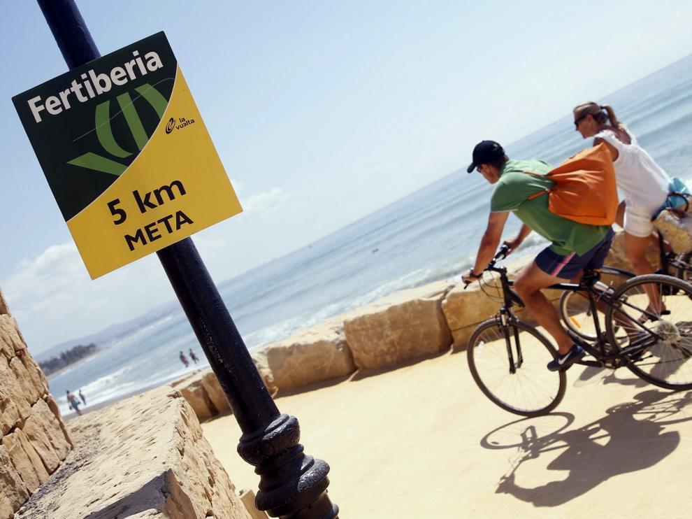 Dos turistas circulan por el paseo marítimo de Puerto Banús por donde este sábado pasará la Vuelta.