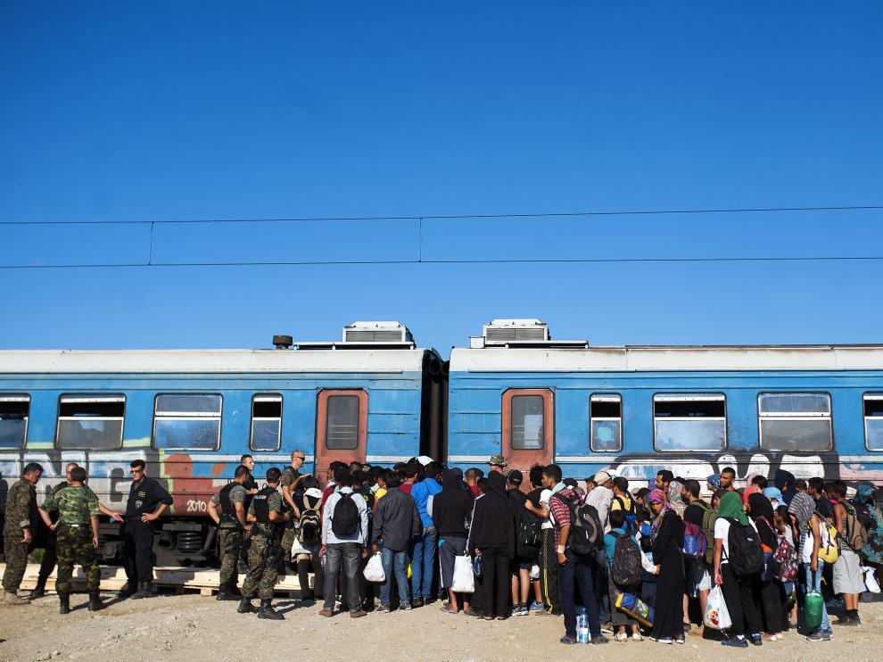 Varios inmigrantes esperan a subirse a un tren para viajar a Serbia.