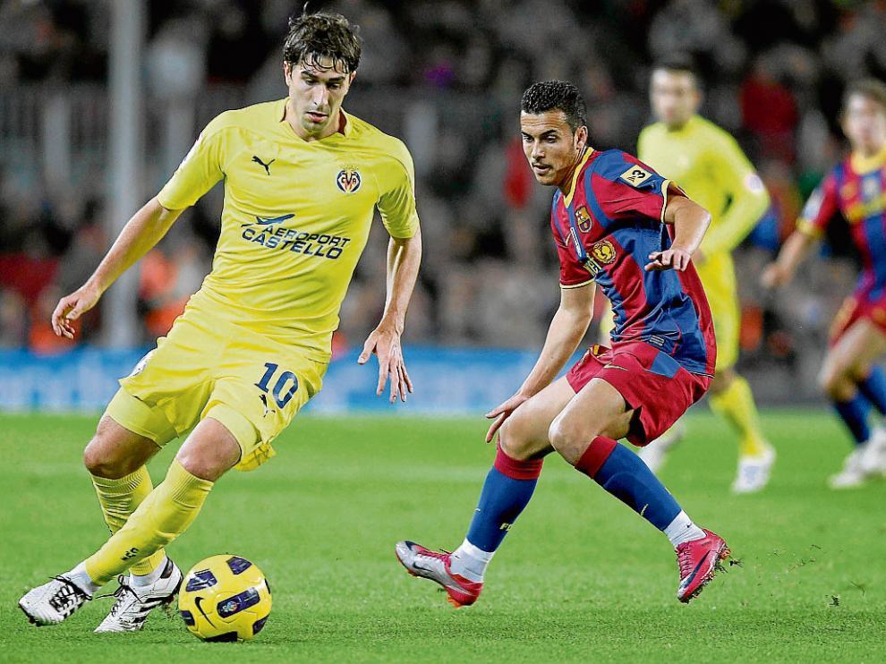 El aragonés Cani protege el balón ante Pedro, durante un partido ante el Barcelona.