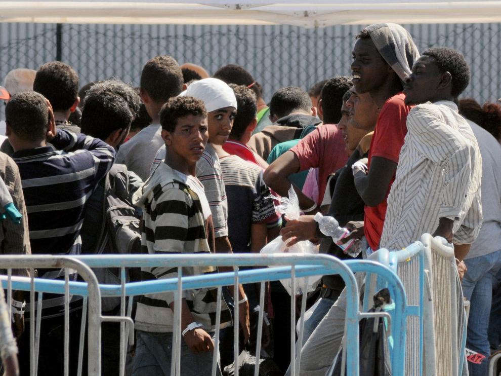 Los inmigrantes esperan tras llegar a la costa italiana.