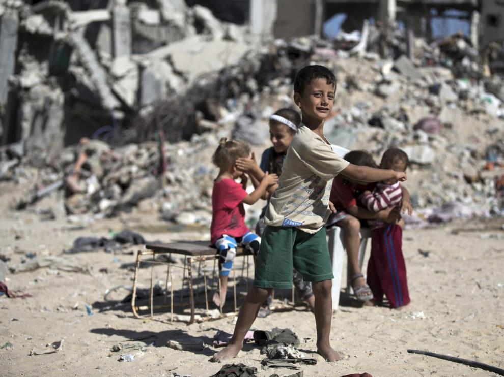 Niños palestinos caminan entre escombros