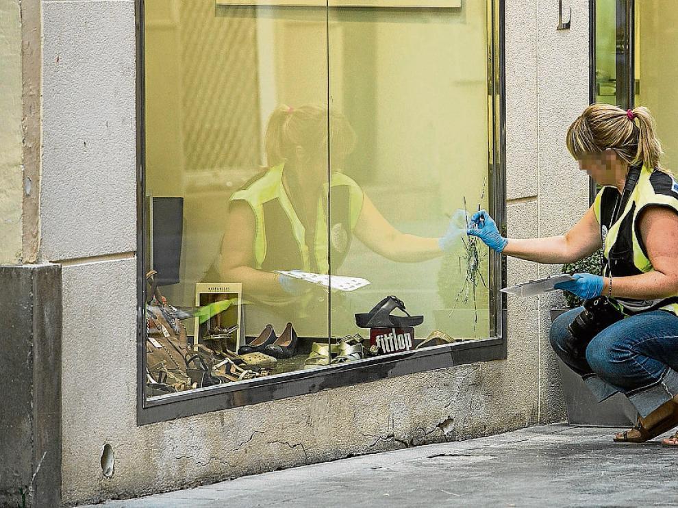 Una agente recoge muestras de los impactos de bala en un escaparate de la calle de Candalija.