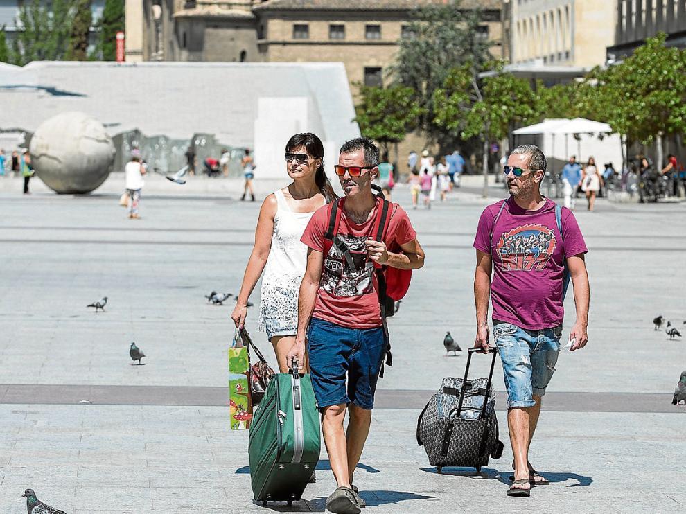 Un grupo de turistas atraviesa la plaza del Pilar, ayer por la mañana.