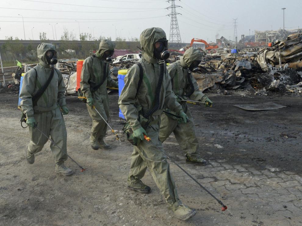 Varios soldados del Ejército de la Liberación del Pueblo de China trabajan para neutralizar los residuos de cianuro de sodio en Tianjin.