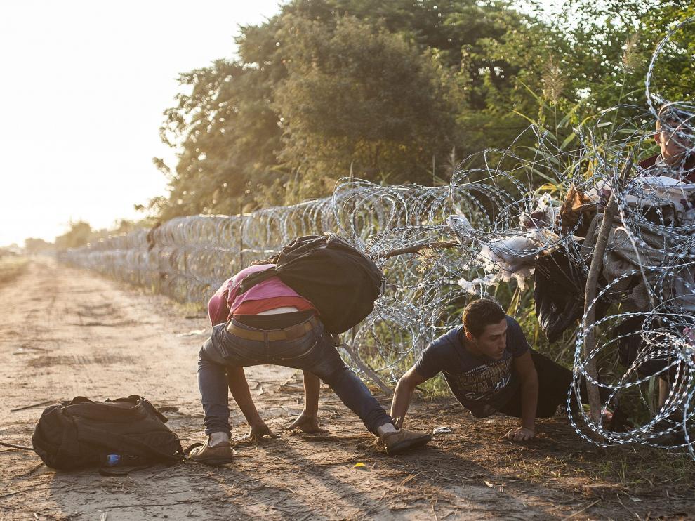 Varios inmigrantes pasan la alambrada que separa Serbia de Hungría
