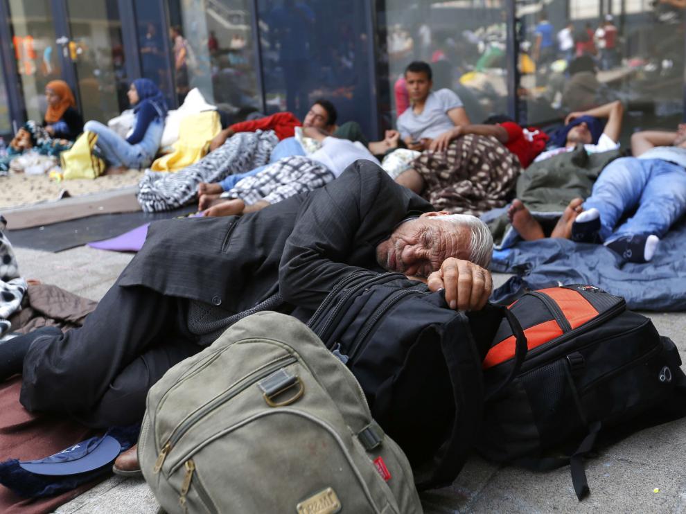 Varios inmigrantes descansan junto a una estación de tren Budapest