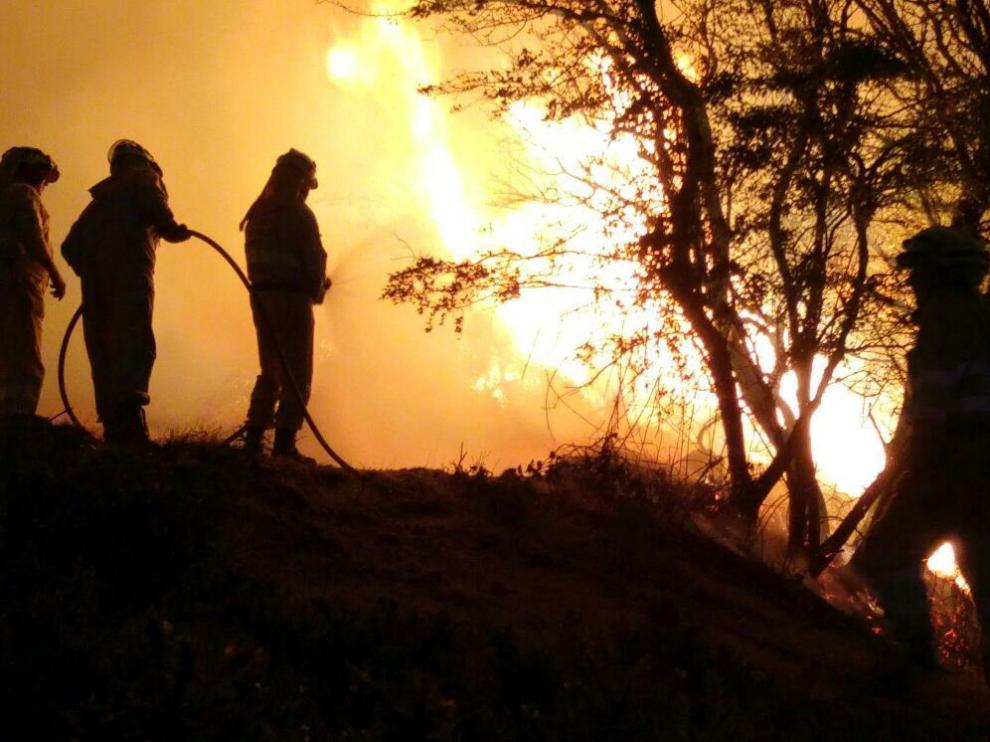 Varios bomberos intentando controlar el incendio declarado en Valderredible.
