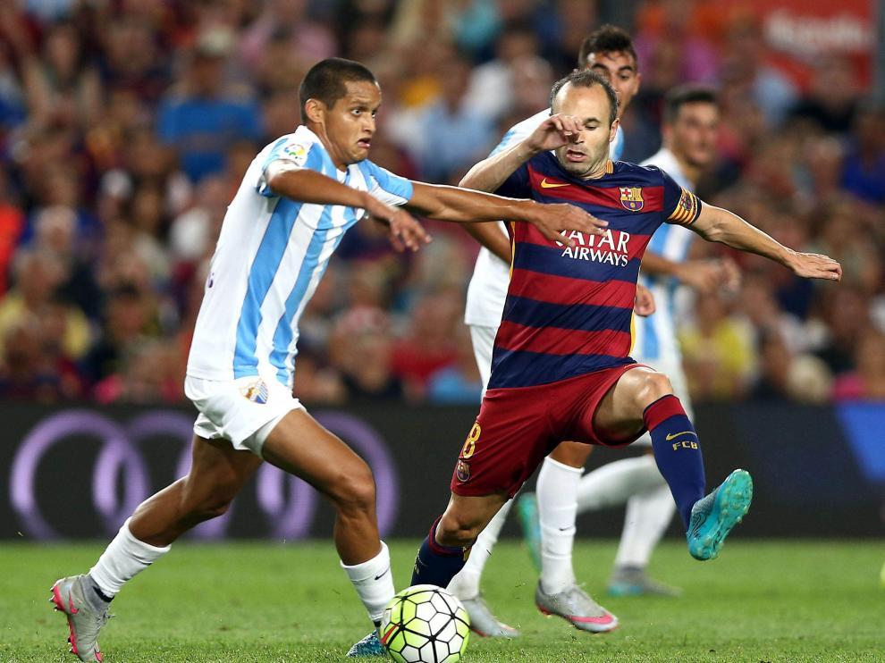 Iniesta lucha el balón con Juanpi, durante el partido de la segunda jornada del Campeonato de Liga.