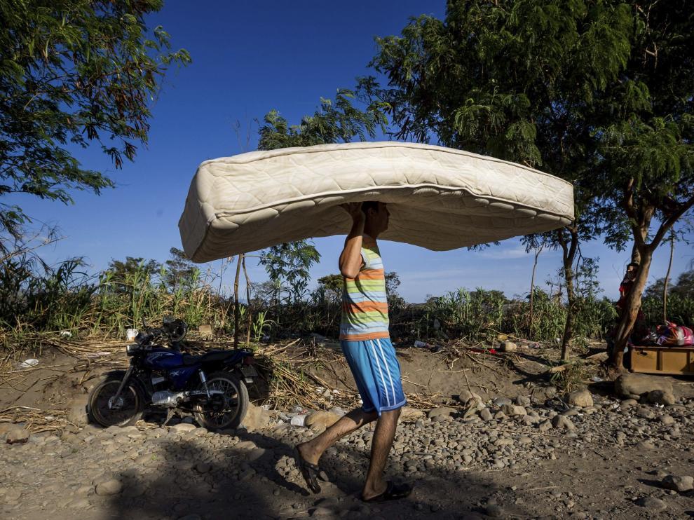 """Un hombre carga con un colchón por una trocha del sector """"La Parada"""" tras cruzar el río Tachira."""